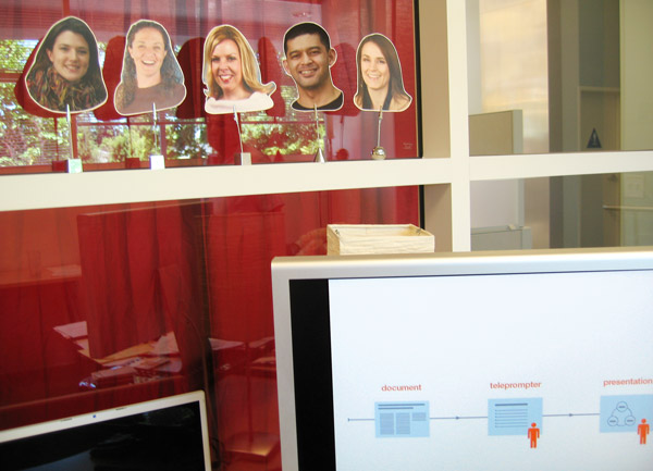 Nancy adding cut out images of her team members to the glass window in her office while she presents