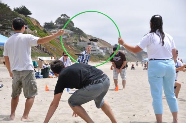 Bullseye! Team members enjoying a frisbee game on the beach