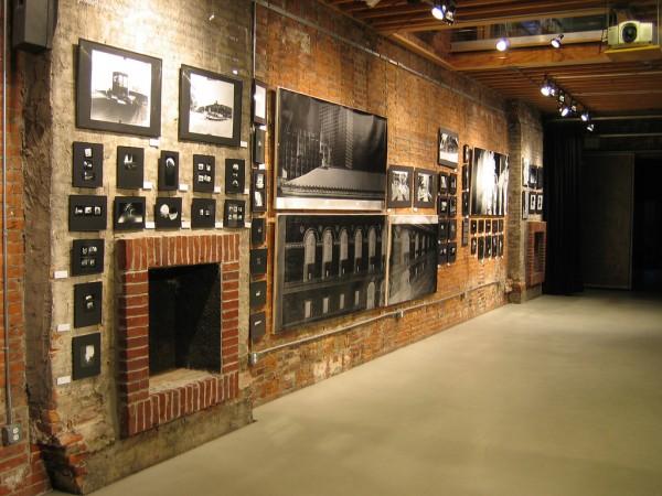 Photos mounted along a brick wall